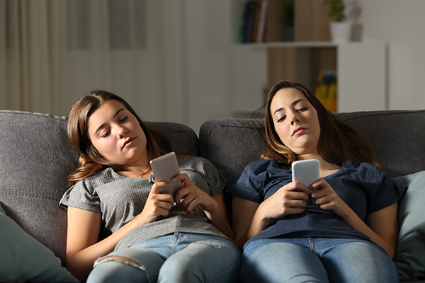 Two teens lay on couch with smartphones looking bored