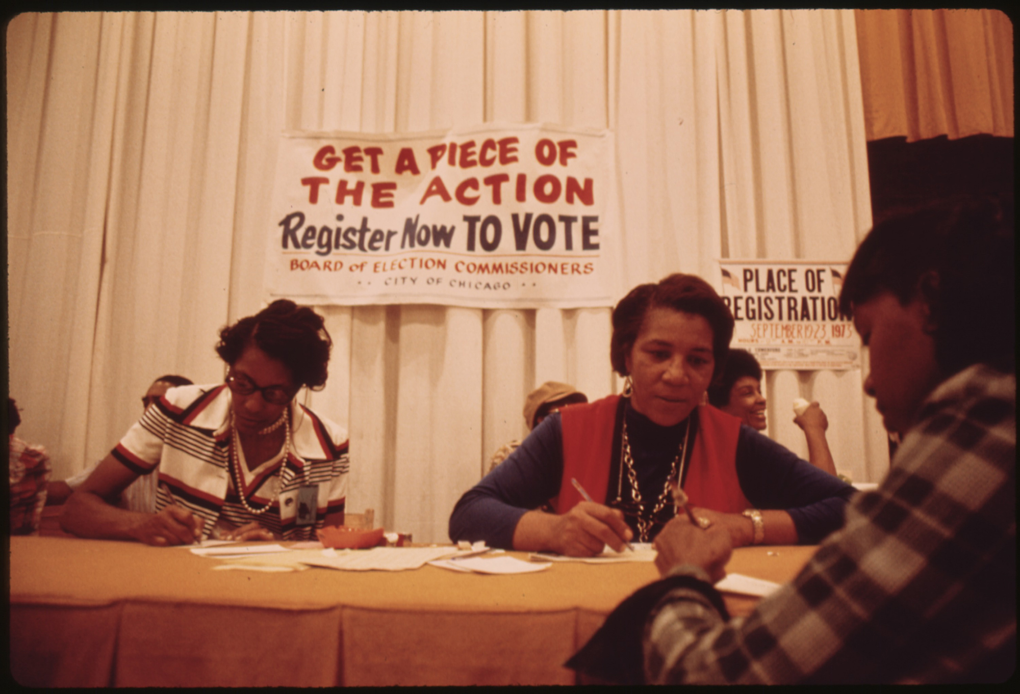 "Two people sign papers registering a third person to vote at the Black Expo in 1973, behind the table a sign reads ""Get a piece of the action Register now TO VOTE"""