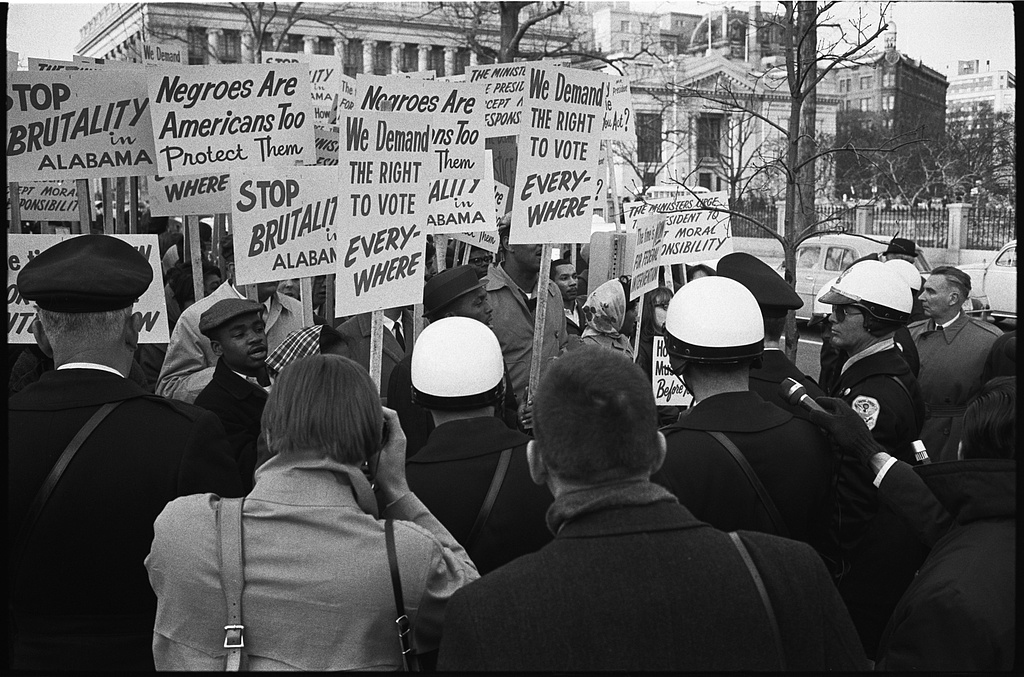 historical photo of a group of people holding protest signs  demanding the right to vote, an end to police brutality.