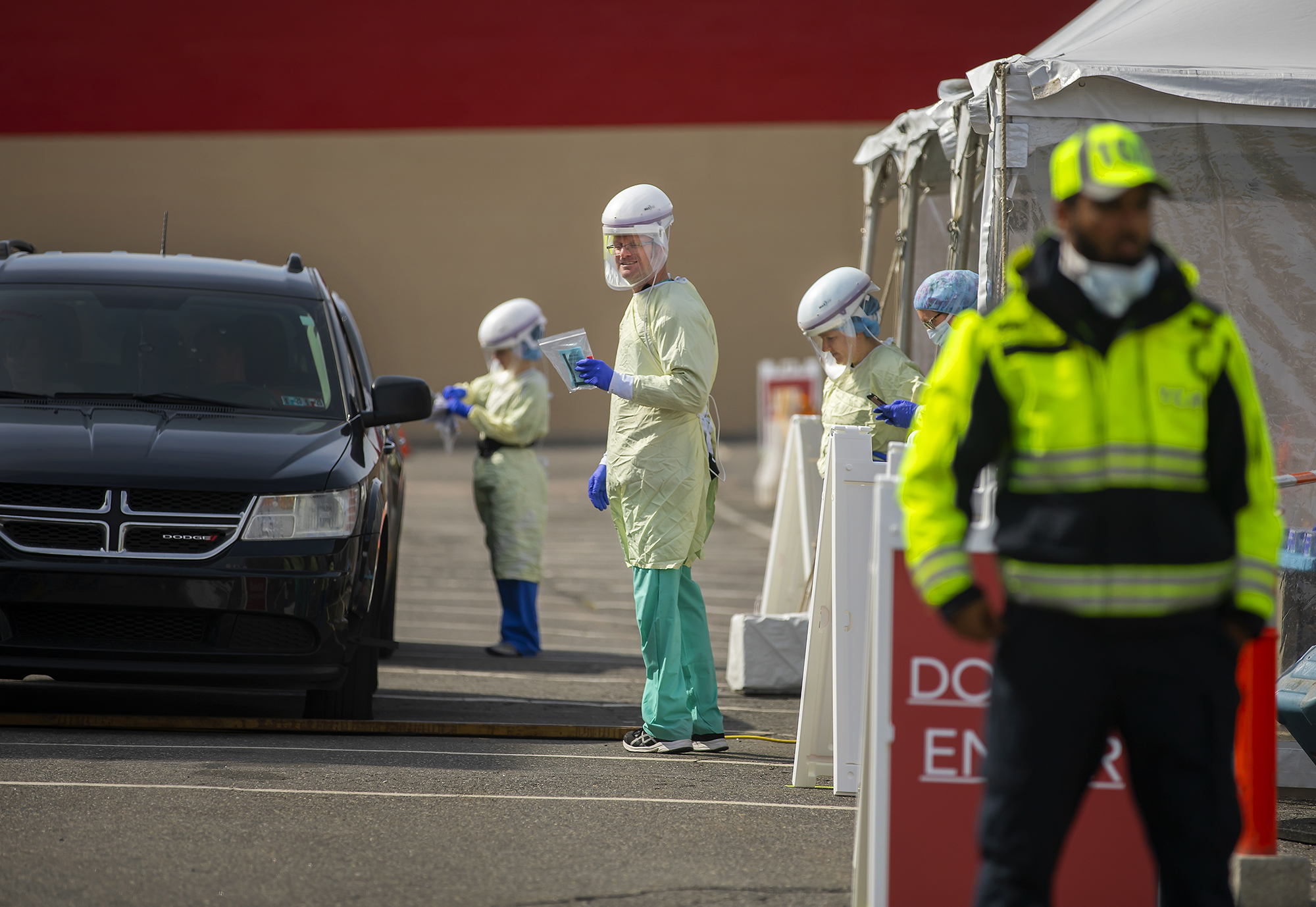 A car in line at drive through testing at the COVID-19 pop up testing site, with four medical personnel outside car in full protective gear and a security guard wearing a medical mask standing at the entrance