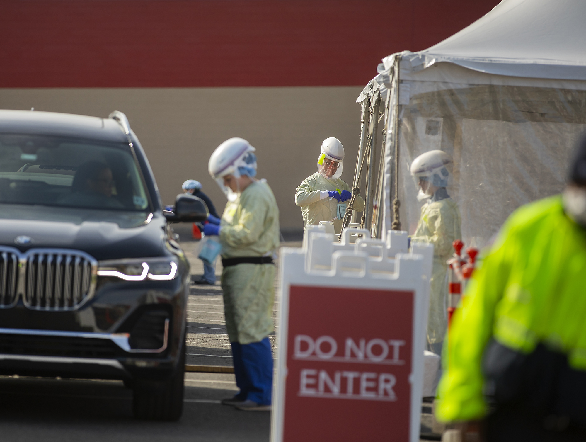 Three medical personnel outside in protective gear working at a drive-through COVID-19 testing site, a Don Not Enter sign in front of the vehicle