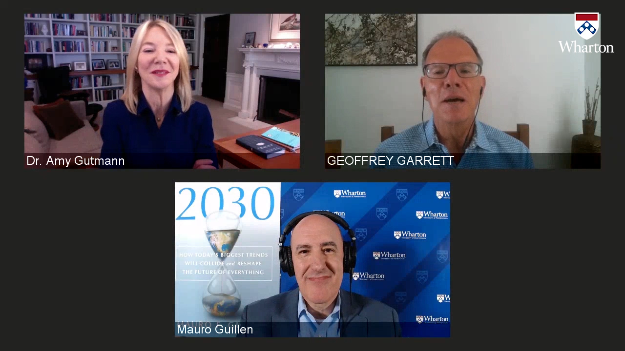 Screen shot of a Zoom screen with Amy Gutmann, Geoffrey Garrett and Mauro Guillen