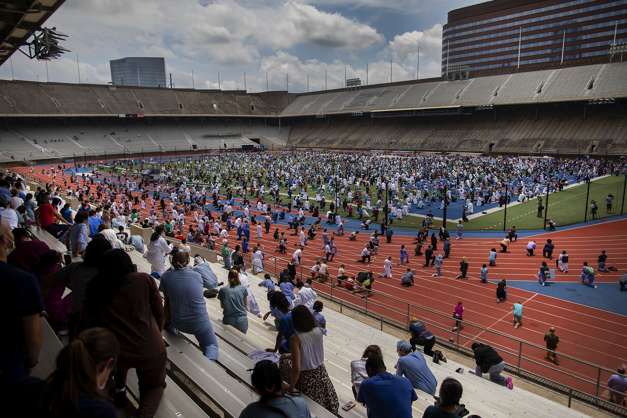 View of Franklin Field from bleachers of Penn Medicine health care workers kneeling in protest.