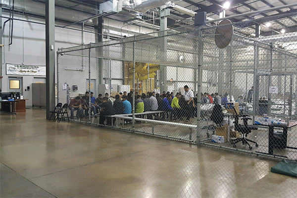 Group of people inside a caged room in an immigration detention center in Texas.