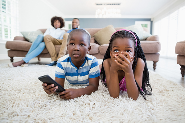 Black family watching television, two children lying on the carpet, two parents on the couch behind them.