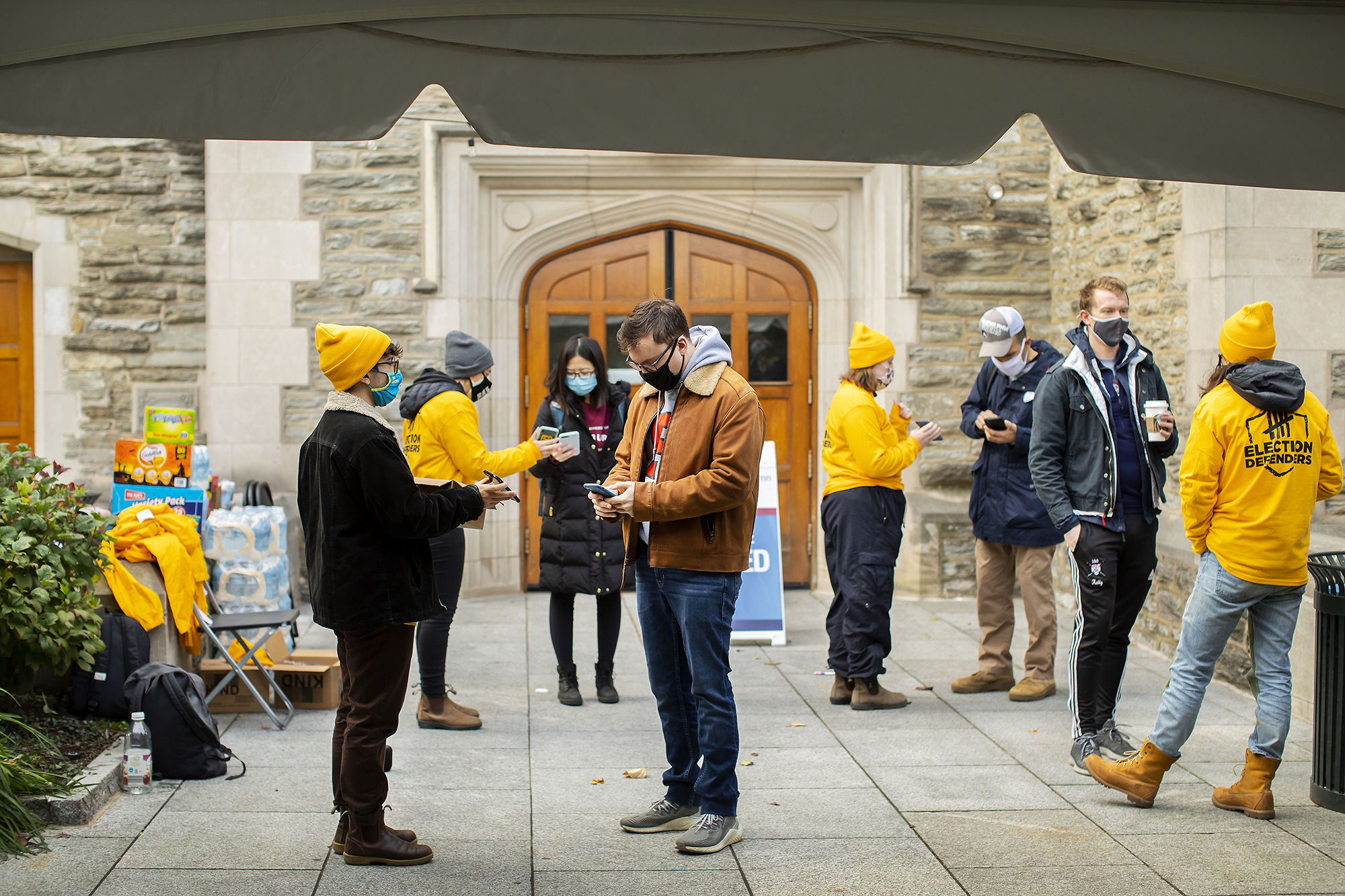 students prepare to vote outside a polling place on campus
