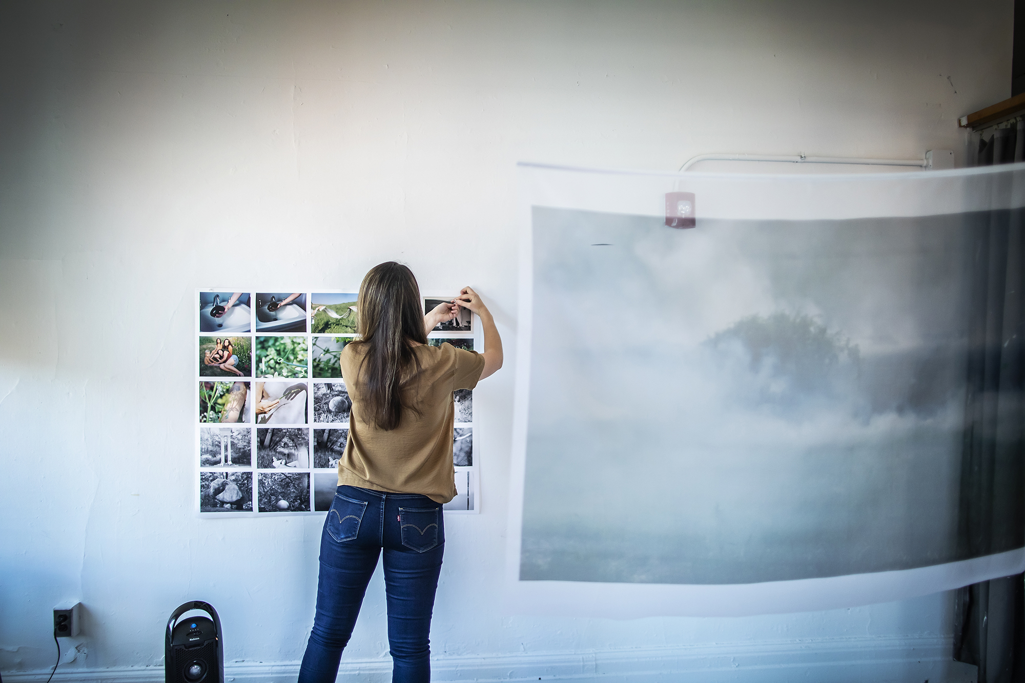 Amrita Stützle in her studio with back turned to camera pins a grid of images to her wall.