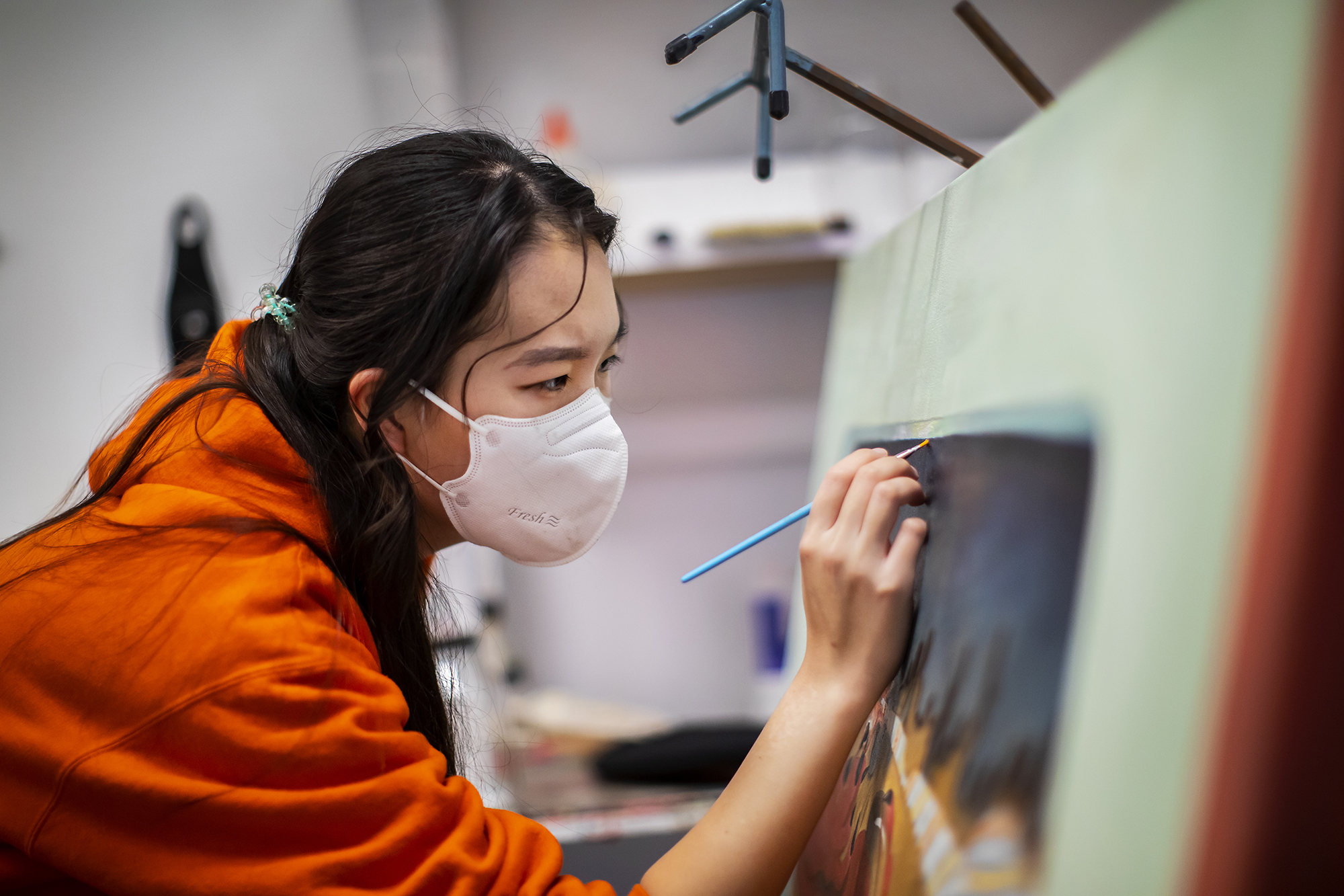 Kay (Seohyung) Lee, wearing a face mask, paints on a canvas in her studio.