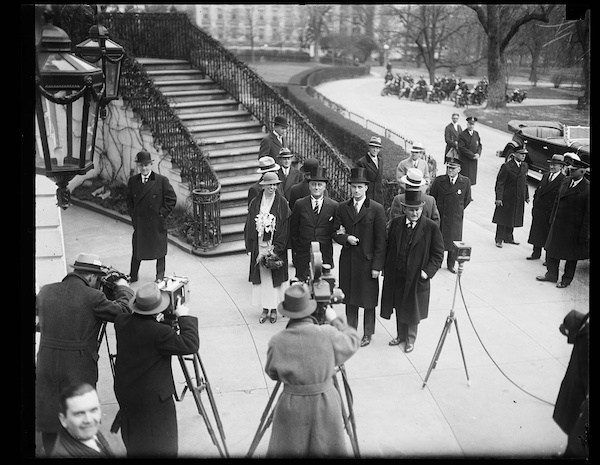 FDR arrives for his 1933 inauguration in a top hat, next to his wife Eleanor as media photographers in fedoras snap photos near the Capitol.