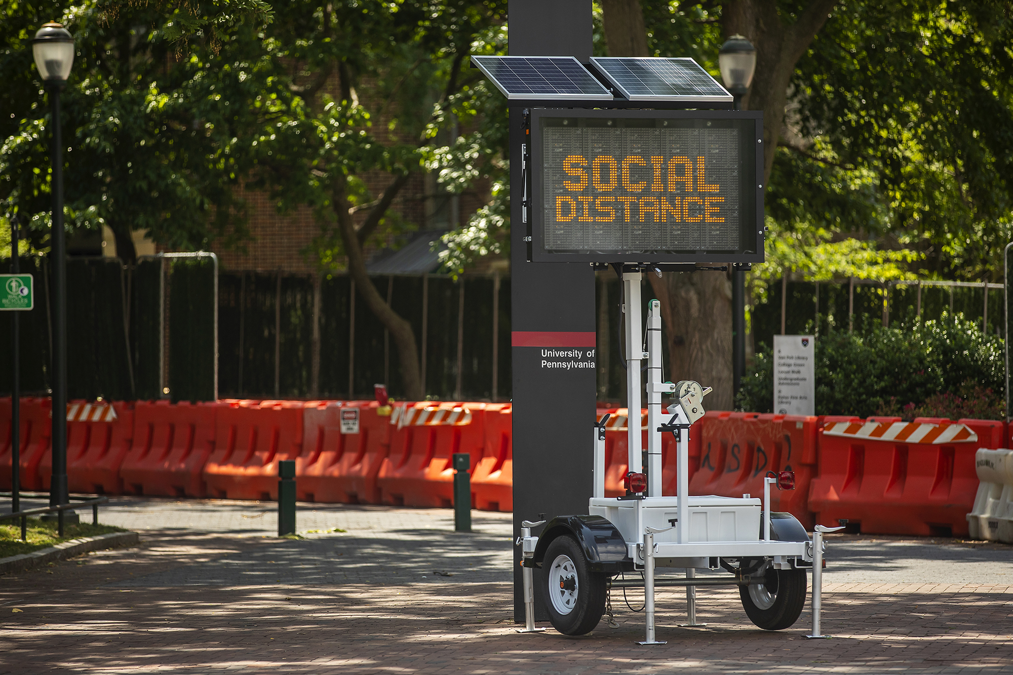 An LED sign on wheels outside a Penn walkway that reads SOCIAL DISTANCE