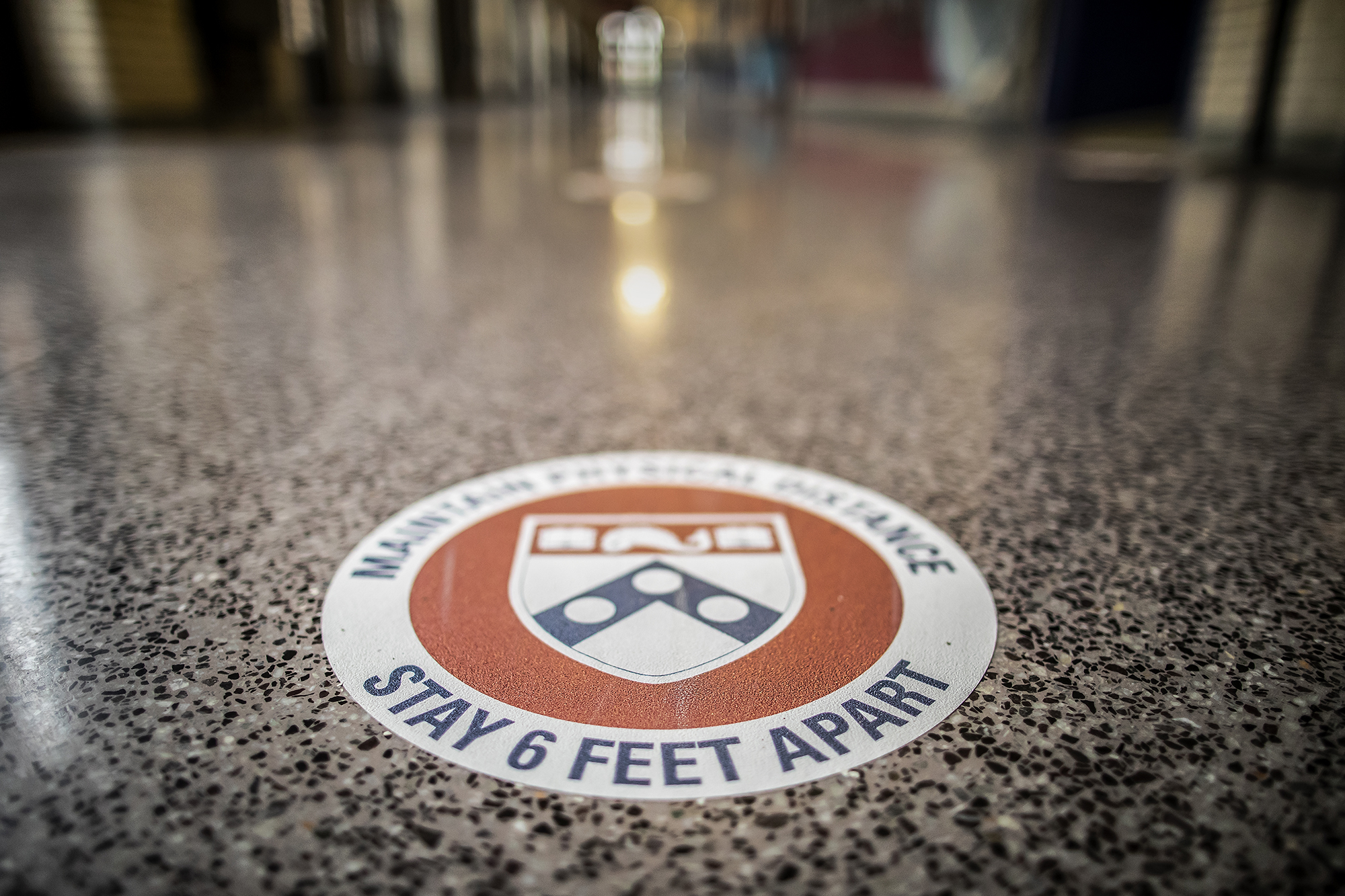 A round decal on the floor that reads MAINTAIN SOCIAL DISTANCE STAY SIX FEET APART surrounding the Penn shield logo.