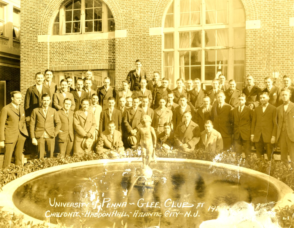 students dressed in coat and tie standing around a fountain