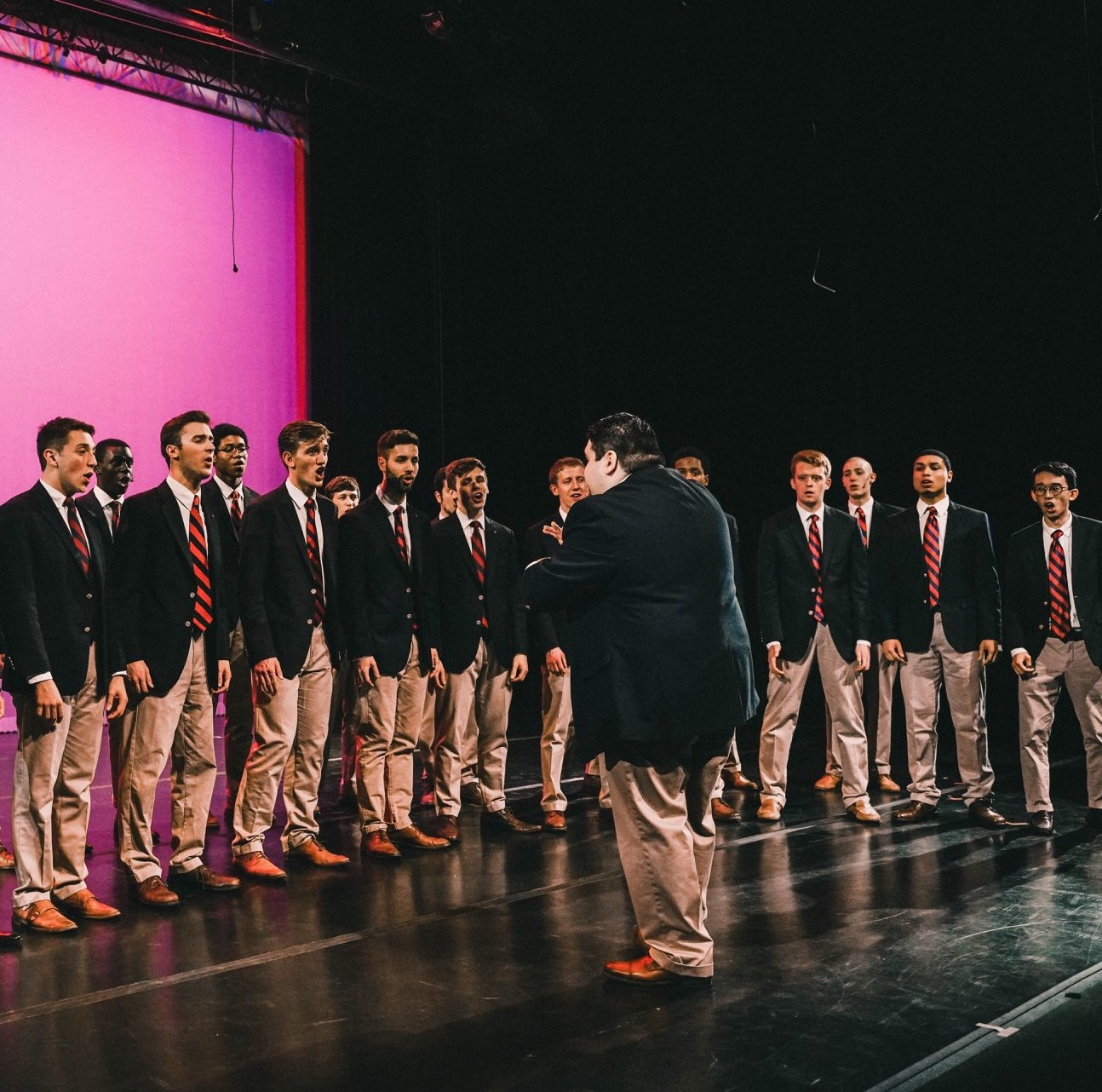 Several students singing while standing on a stage