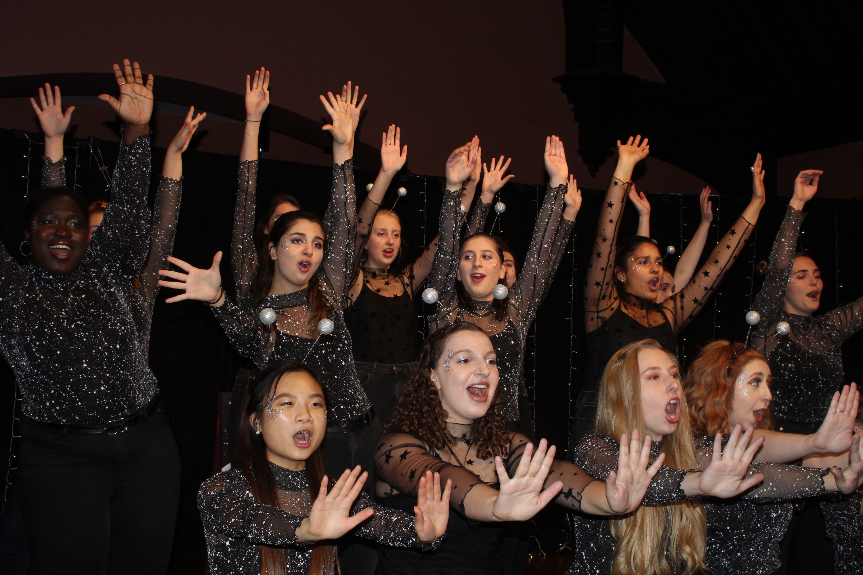 students singing with hands up