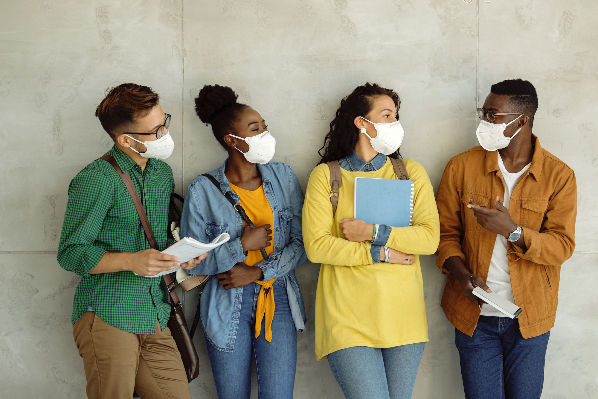 A group of four people leaning against a wall. The one farthest on the left is wearing a bag diagonal across the chest and holding papers. The second from left has on a purse. The second from right has on a backpack and is holding a blue spiral notebook. The person all the way on the right is pointing to the others and holds a folded piece of white paper and a writing utensil.