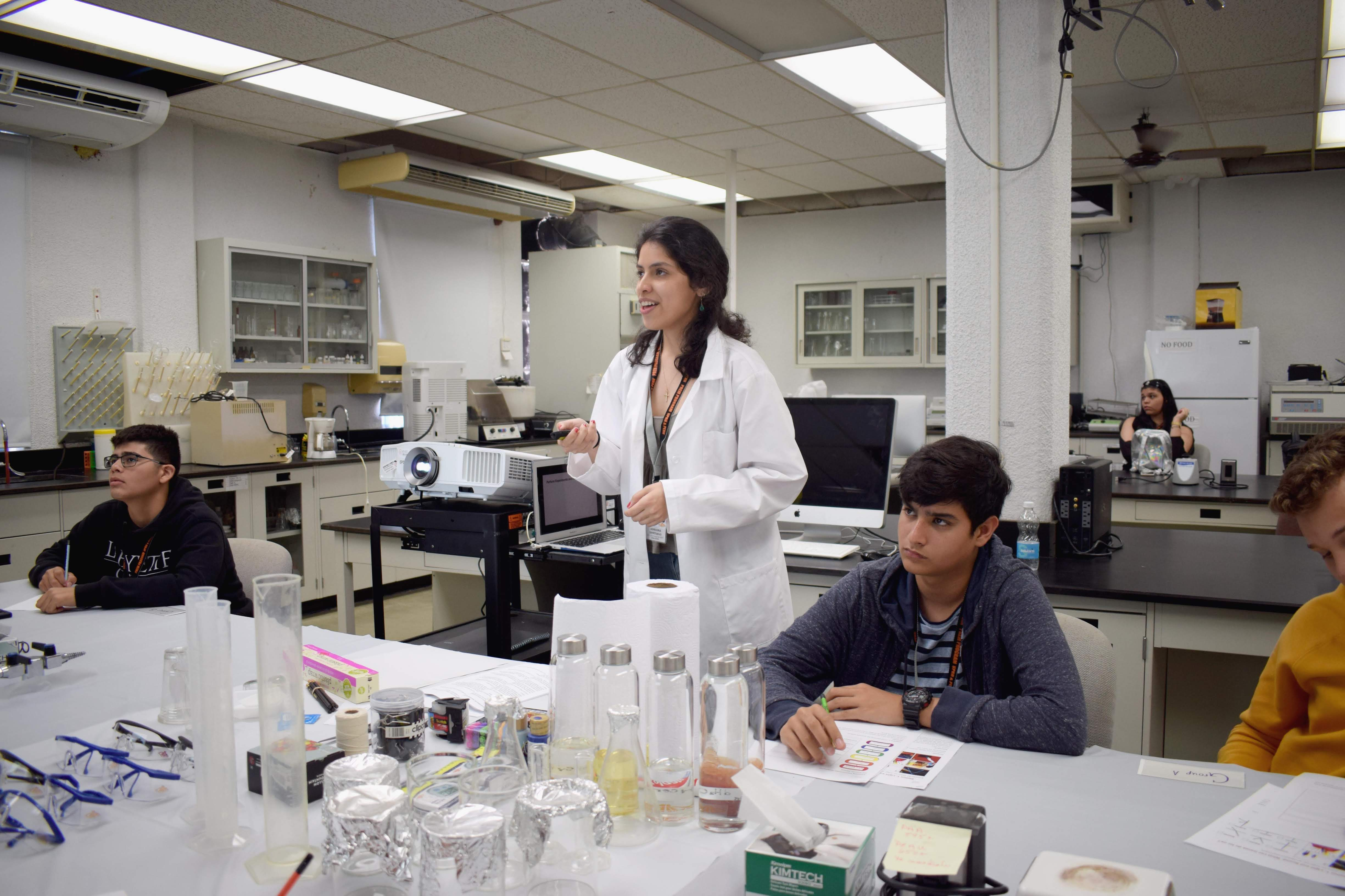 a person wearing a lab coat gives a lecture to students in a lab