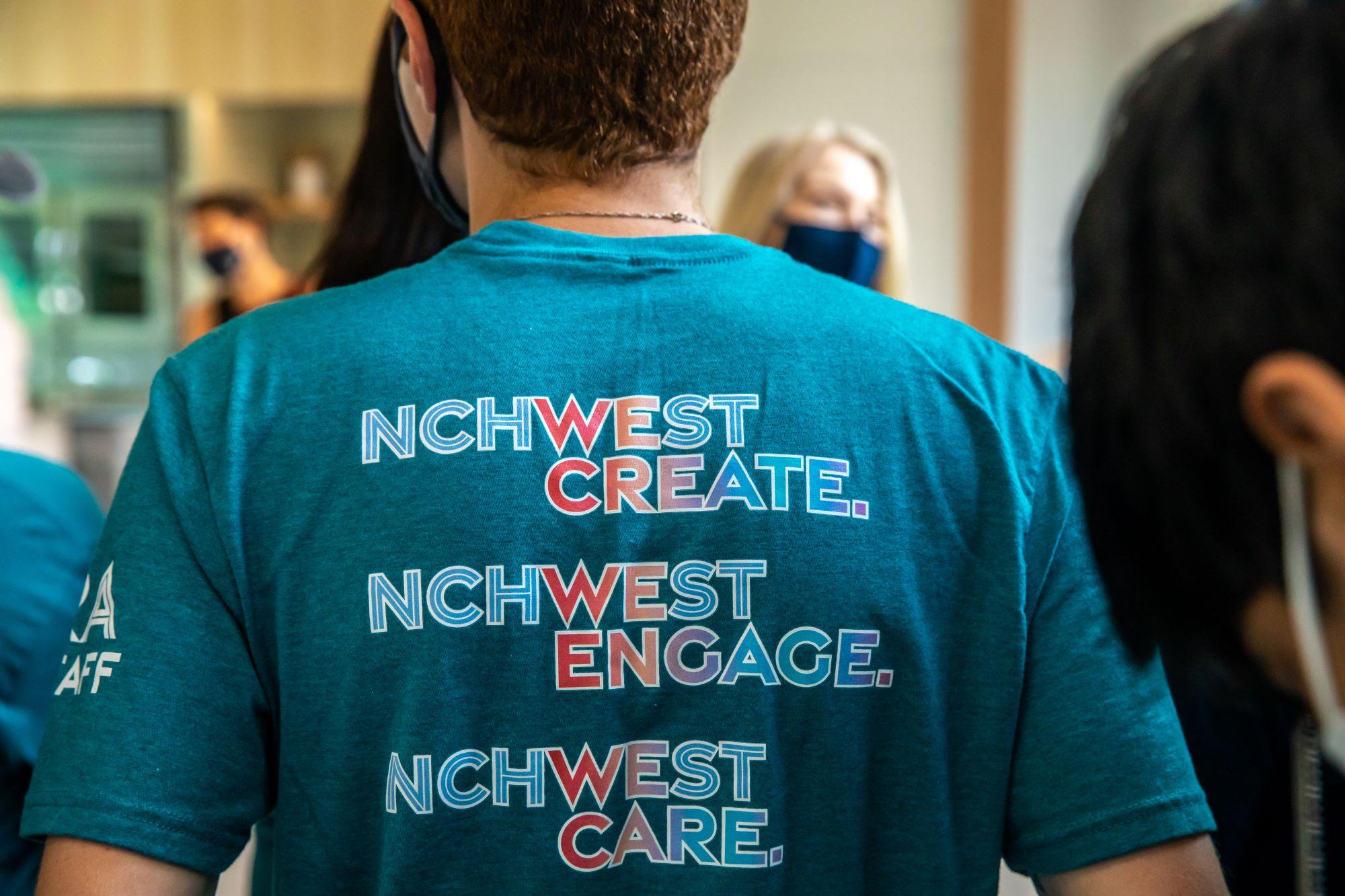 Back of T-shirt that reads NCHWest Create, NCHWest Engage, NCHWest Care