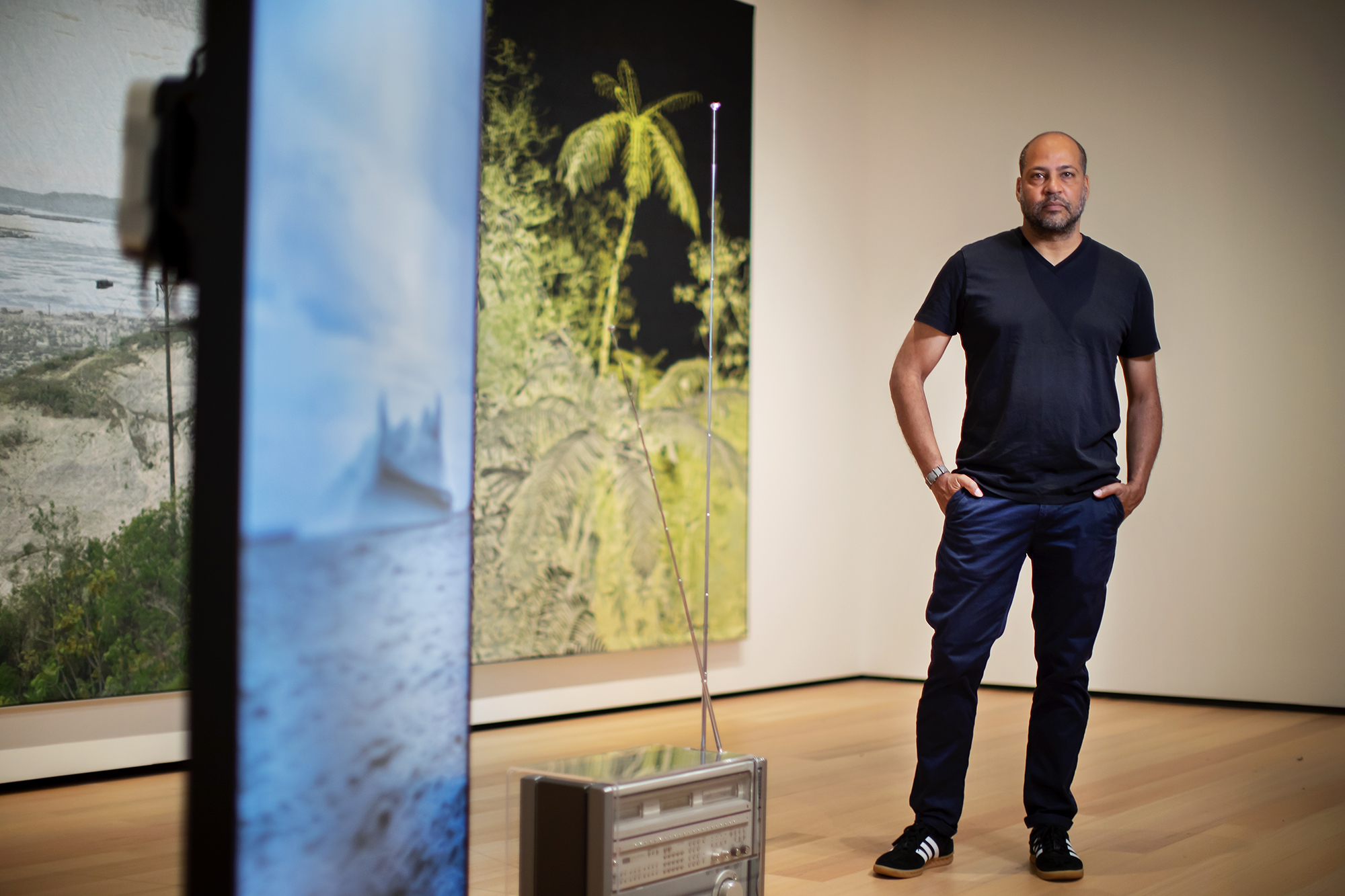 Artist standing in museum gallery with his artwork installation