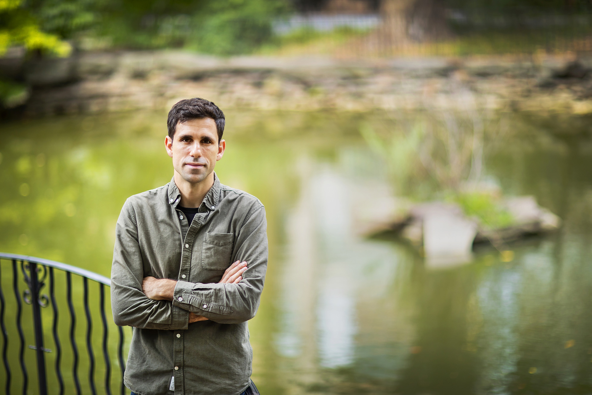 person with arms crossed in front of pond