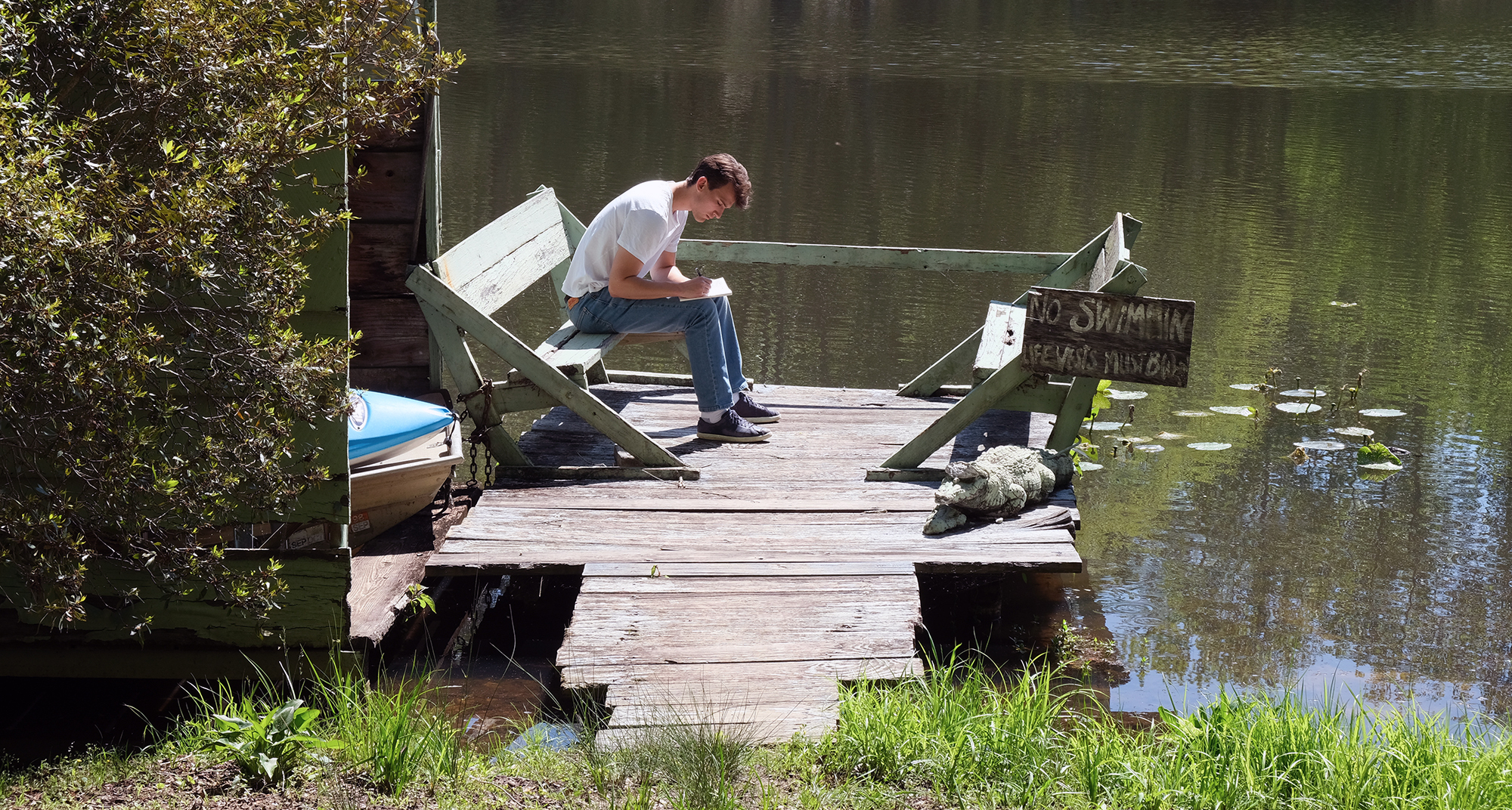 Max Strickberger on a dock writing