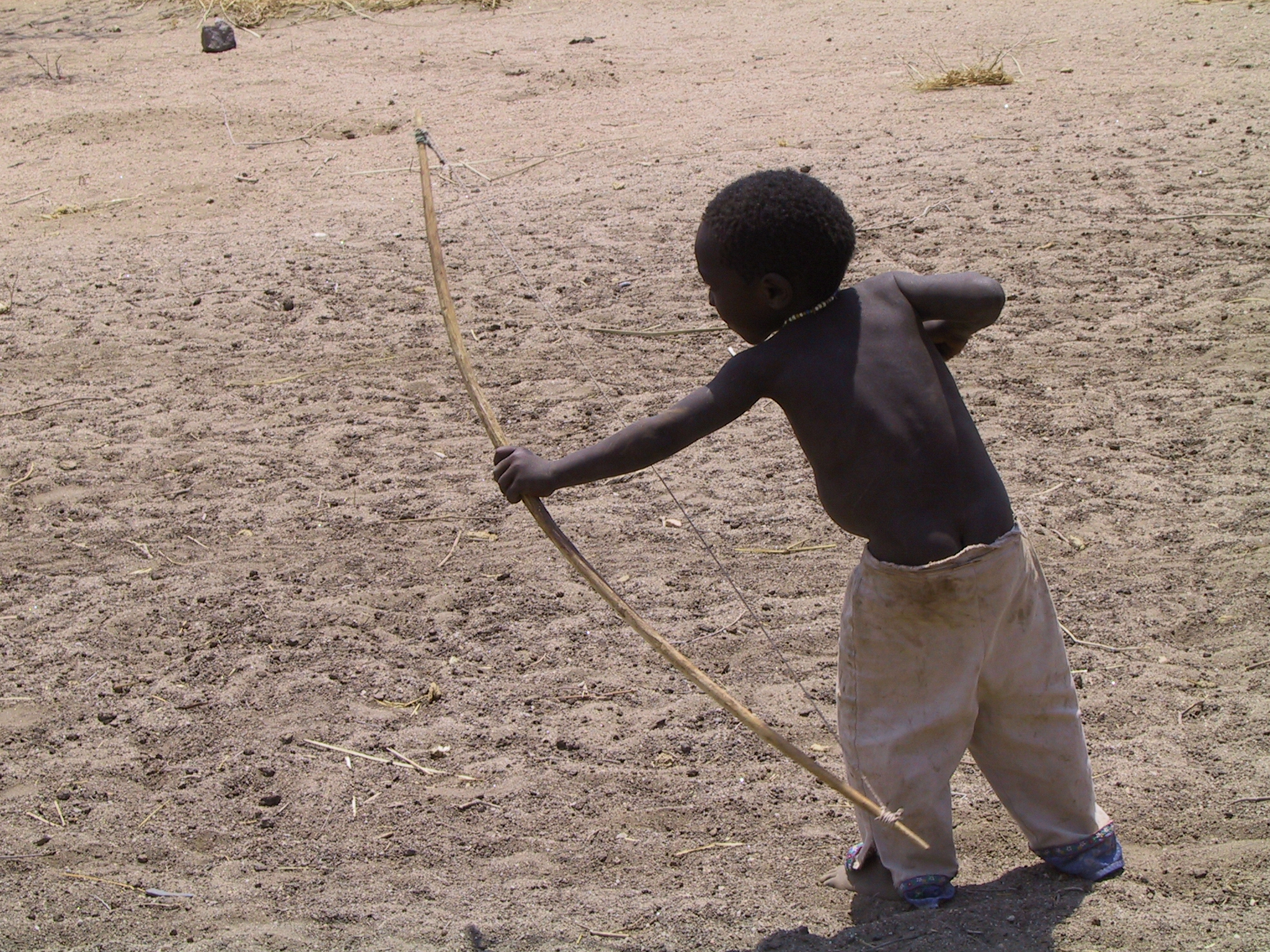 A member of the Hadza tribe of Tanzania, a young boy practices his archery skills.