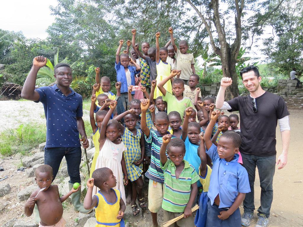 Frimpong (far left) and Scott Aker (far right) visit with children in Tarkwa Breman.