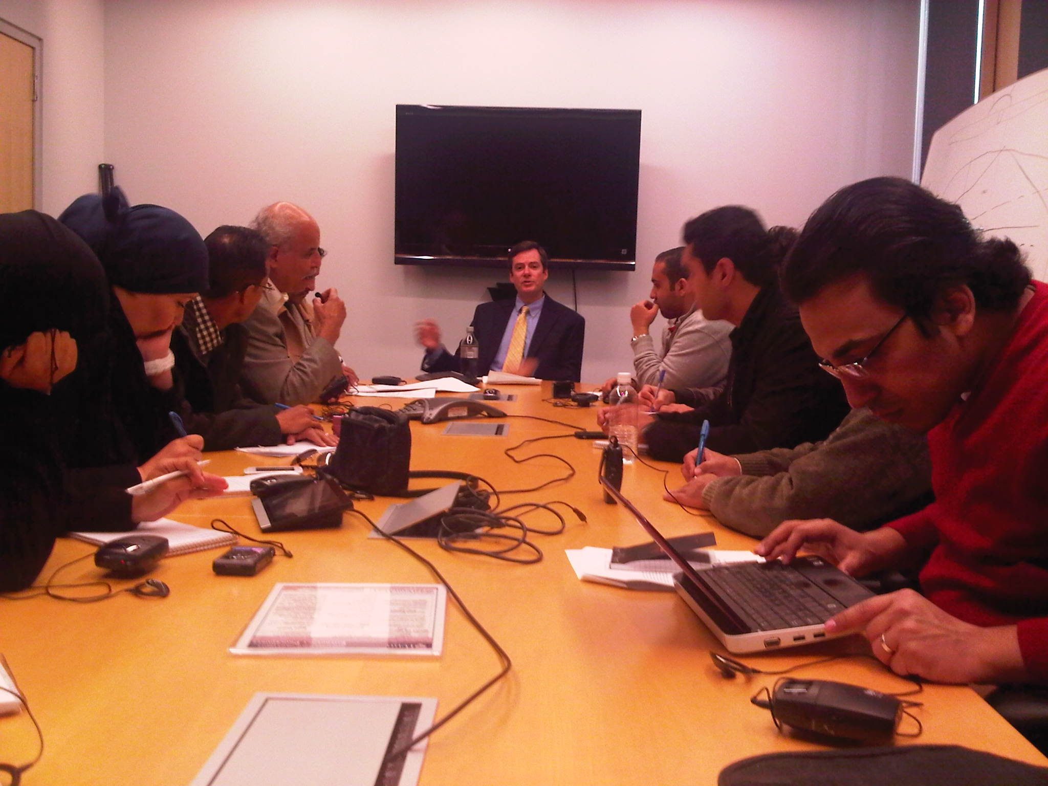 Journalists from Egypt, Libya, Tunisia and Yemen covering the U.S. election speak with FactCheck.org's Rob Farley, center.