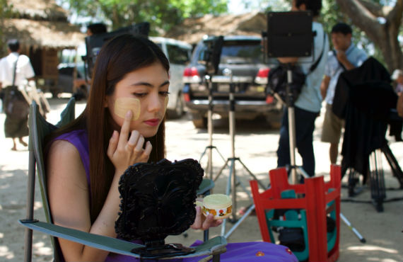 Myanmar actress prepares to play a village girl by putting on traditional Thanaka (tree bark) face makeup