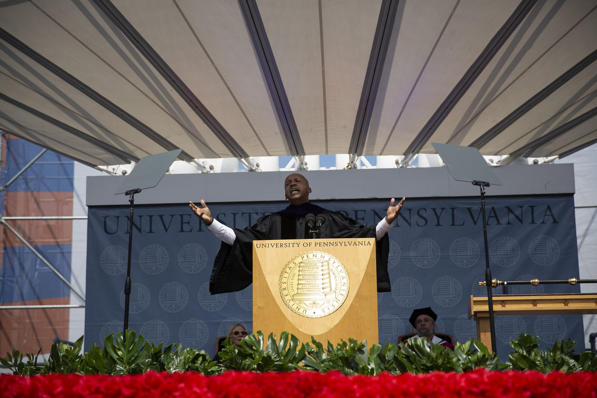 Bryan Stevenson reaches his arms out wide while speaking at a podium on stage at commencement.