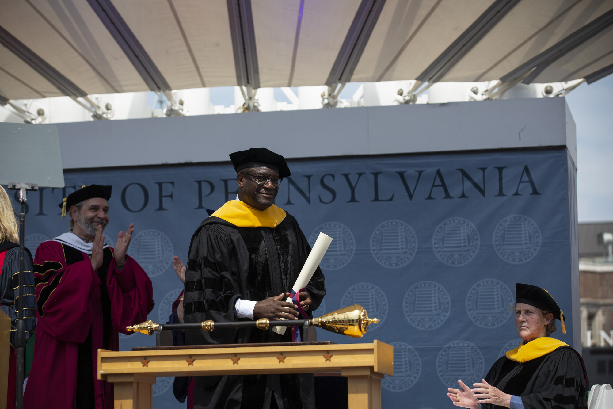 Michael Delli Carpini claps as Denis Mukwege holds his honorary degree, with Temple Grandin seated and clapping.