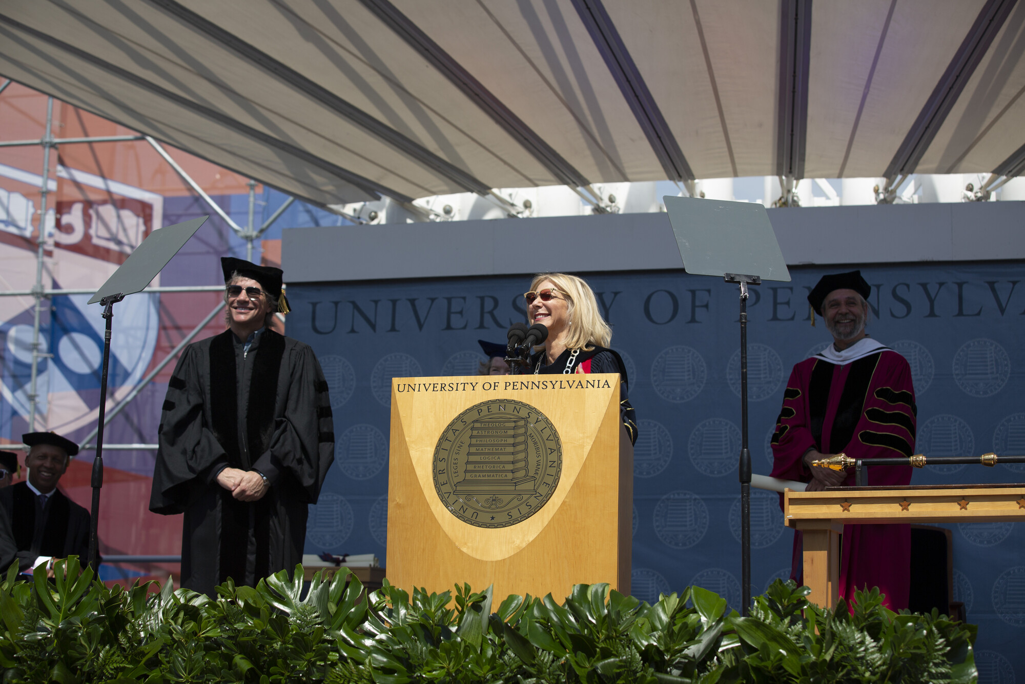 Jon Bon Jovi, Amy Gutmann and Michael Delli Carpini on stage during commencement, Gutmann is at a podium.