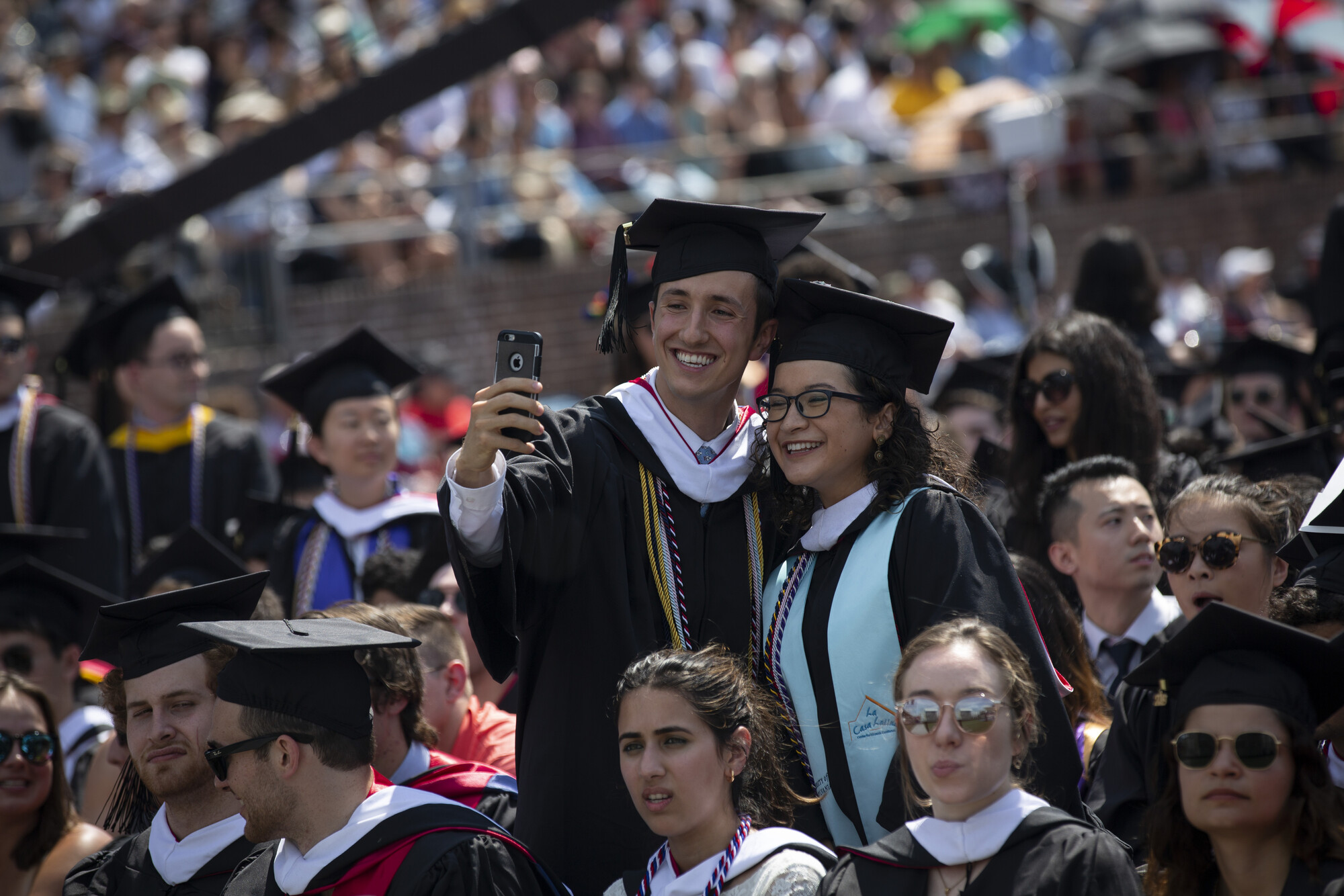Two graduating students stand and take a selfie on the field during commencement