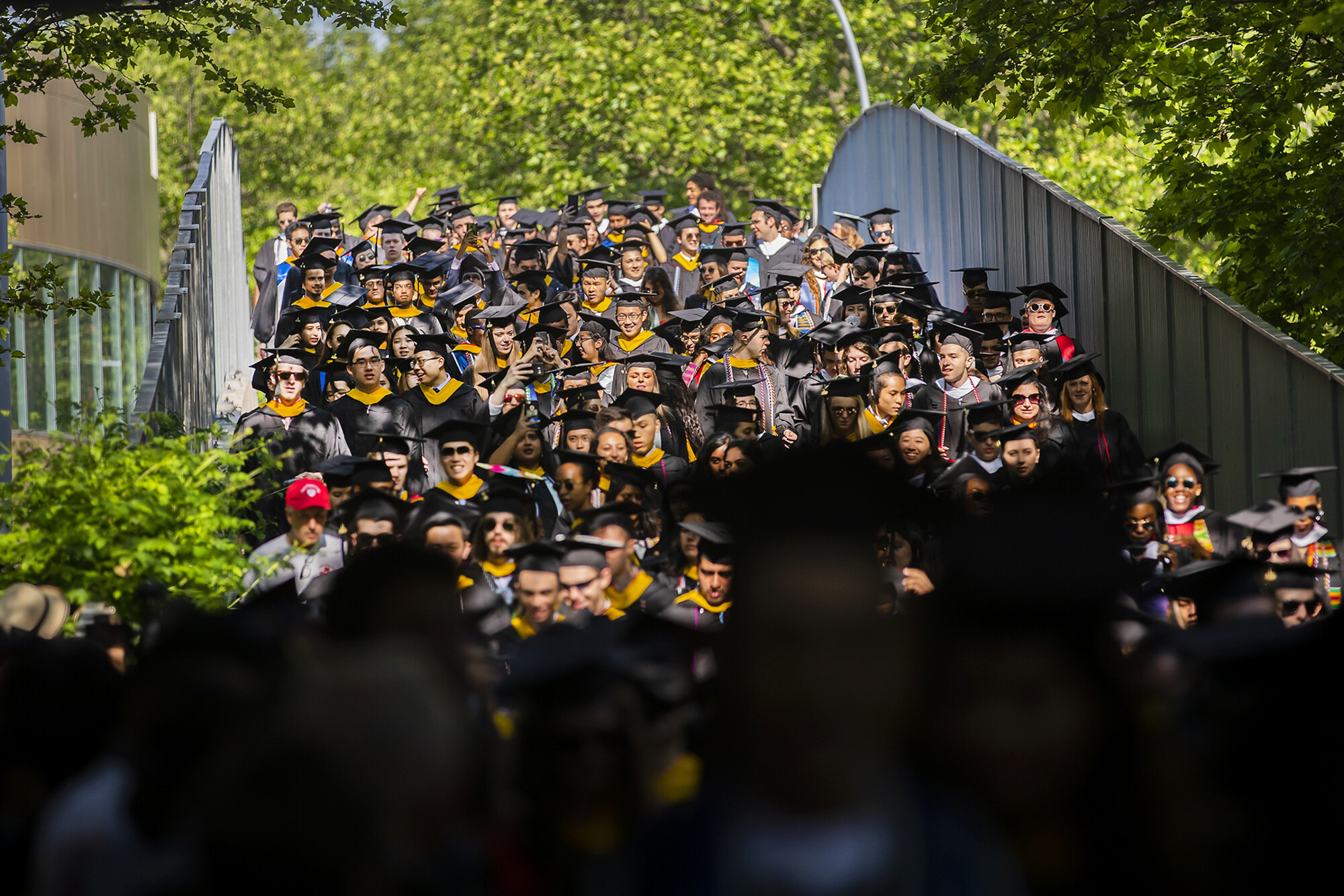 Procession of graduates down Locust Walk Bridge.