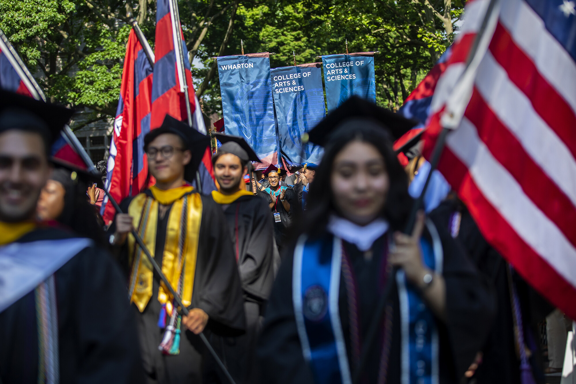Graduates holding flags in procession down Locust Walk.