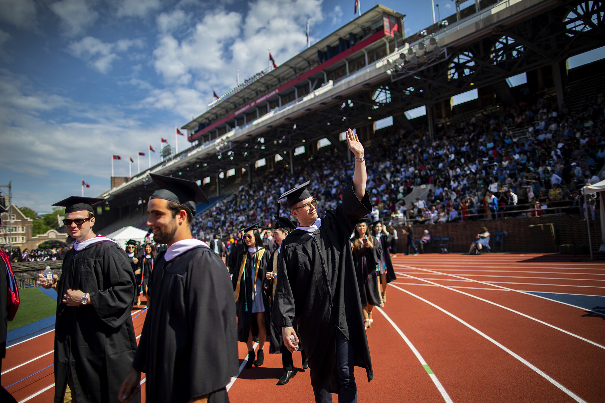 Graduates arrive on Franklin Field, one waving to audience.