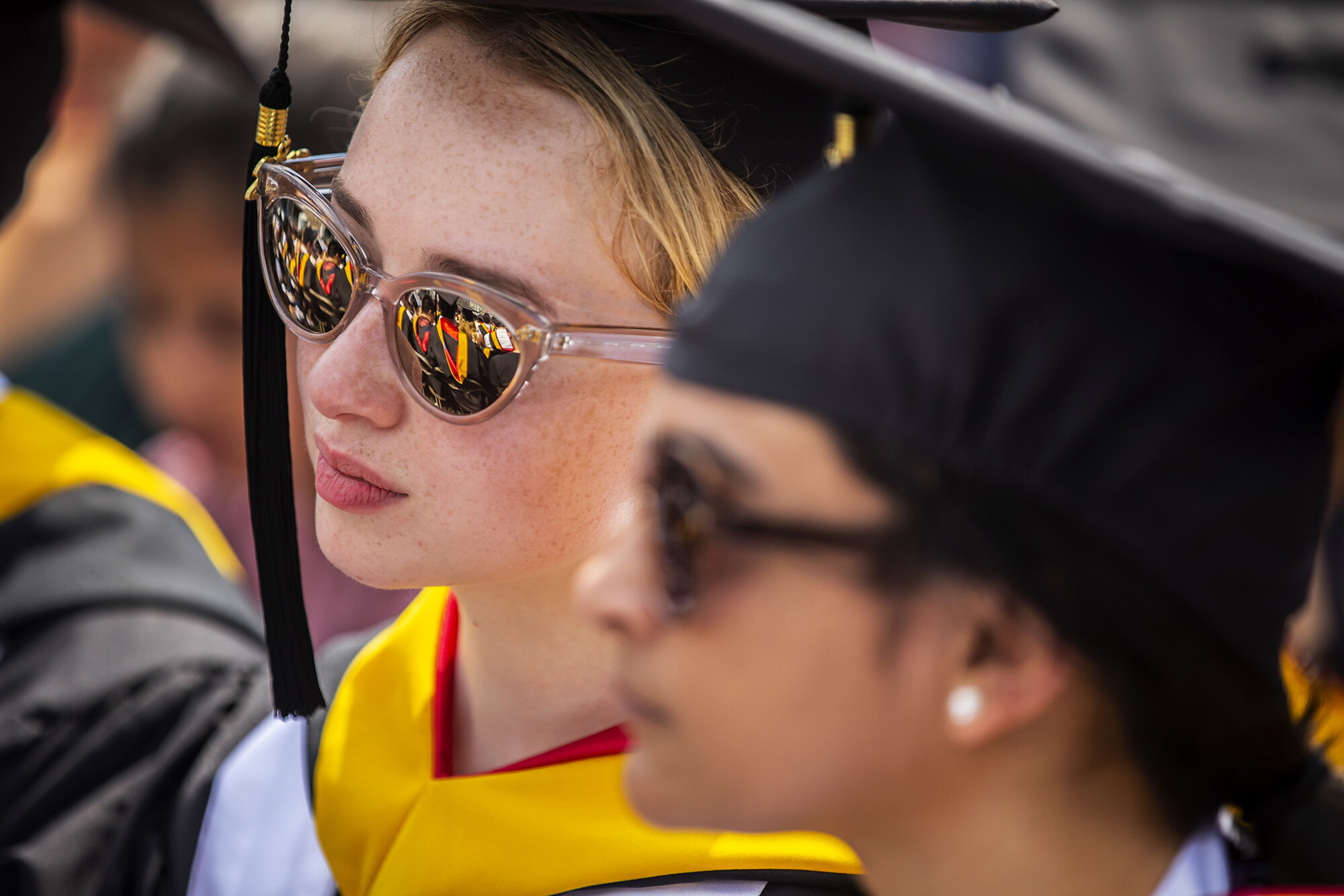Graduate in sunglasses seated with reflection of other graduates in sunglasses.