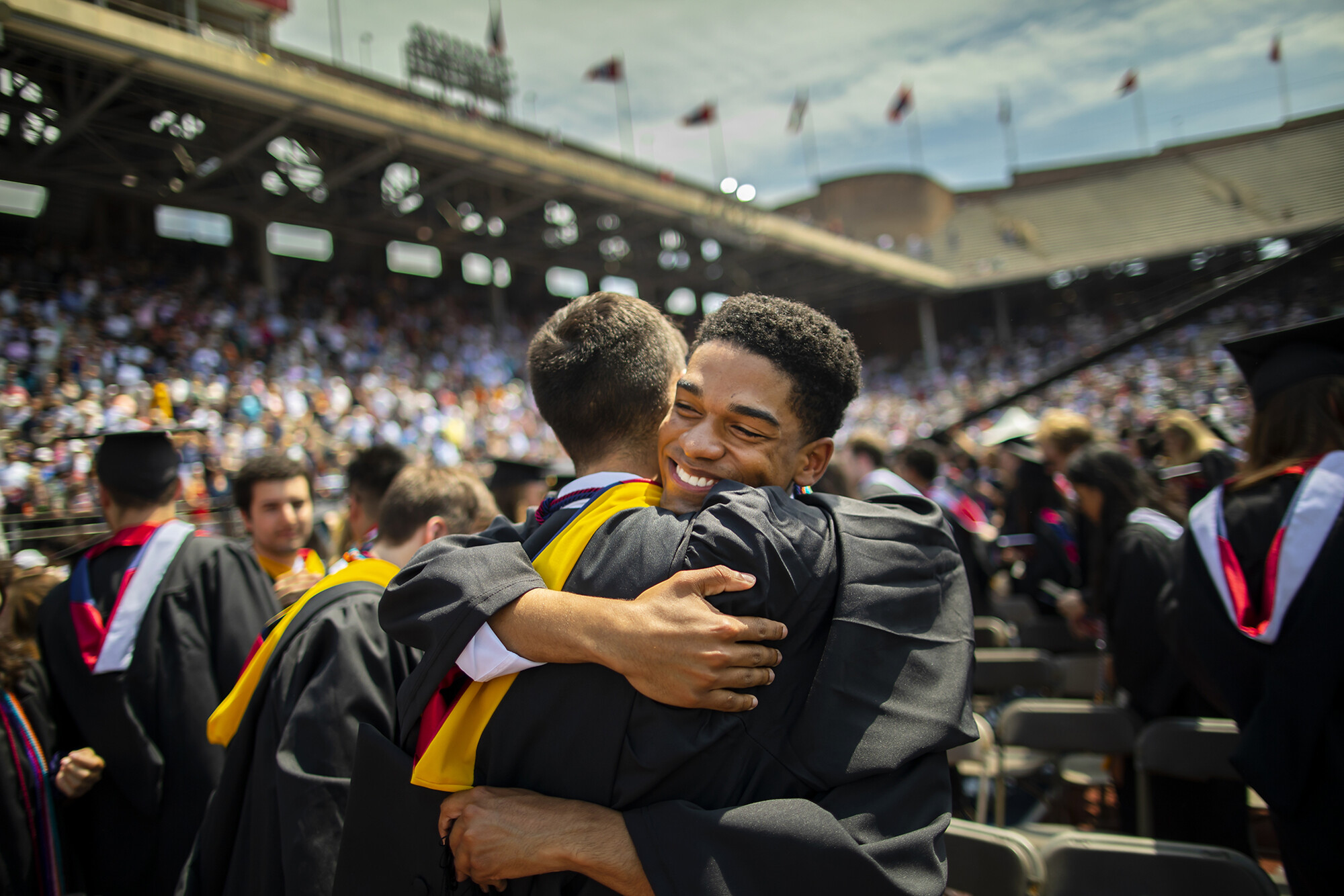 Two graduates embrace on the field at commencement.