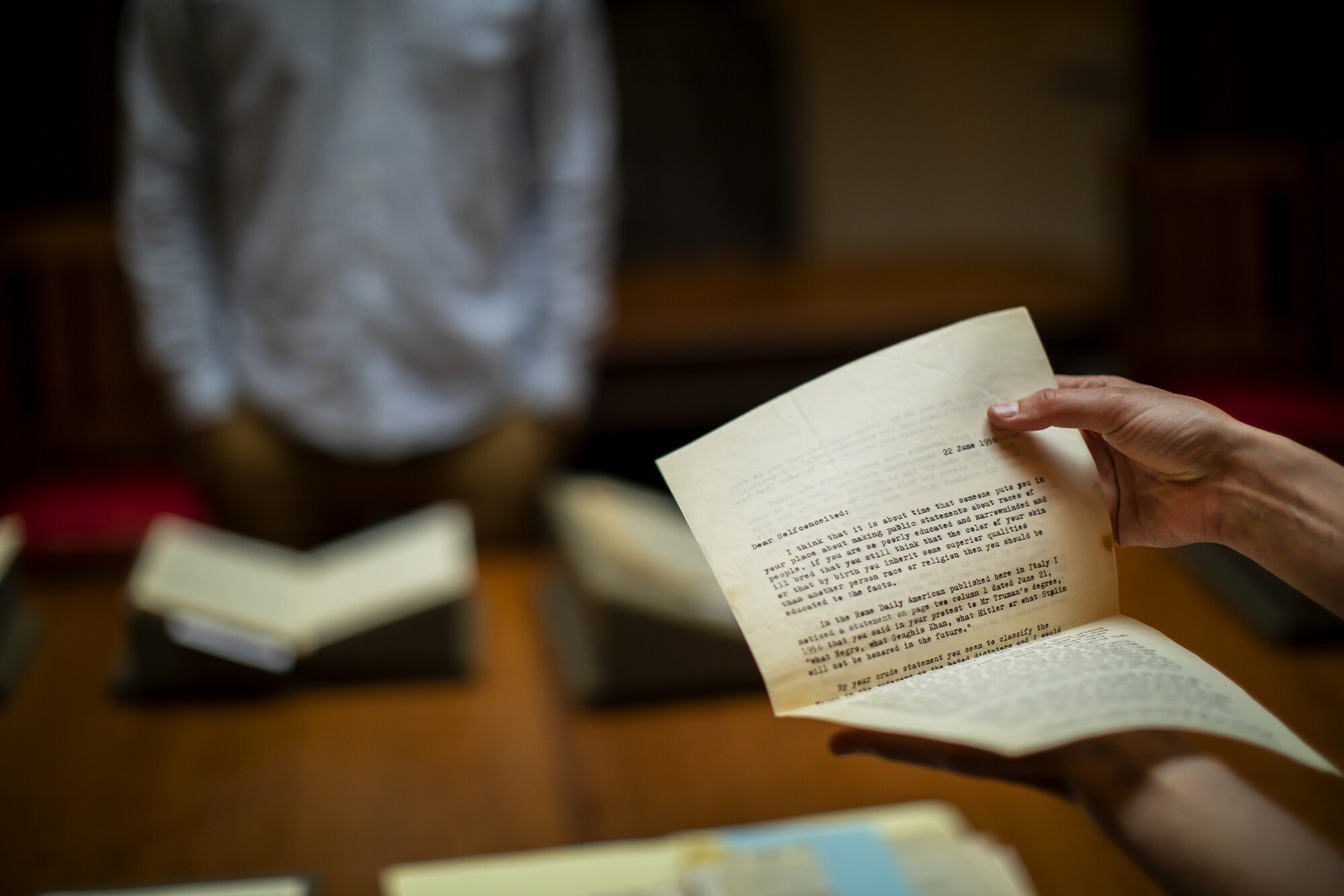 Typed letter, many pages thick, being held by two hands. A blurred figured standing in front of a book is in the background.