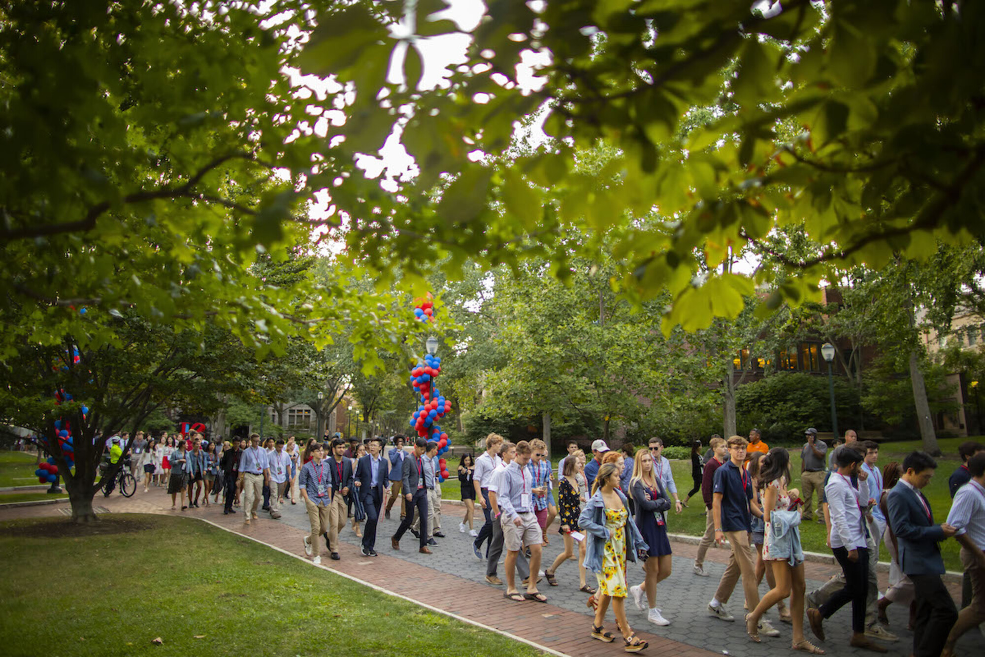 Class of 2023 walks down Locust Walk at dusk towards convocation on College Green.