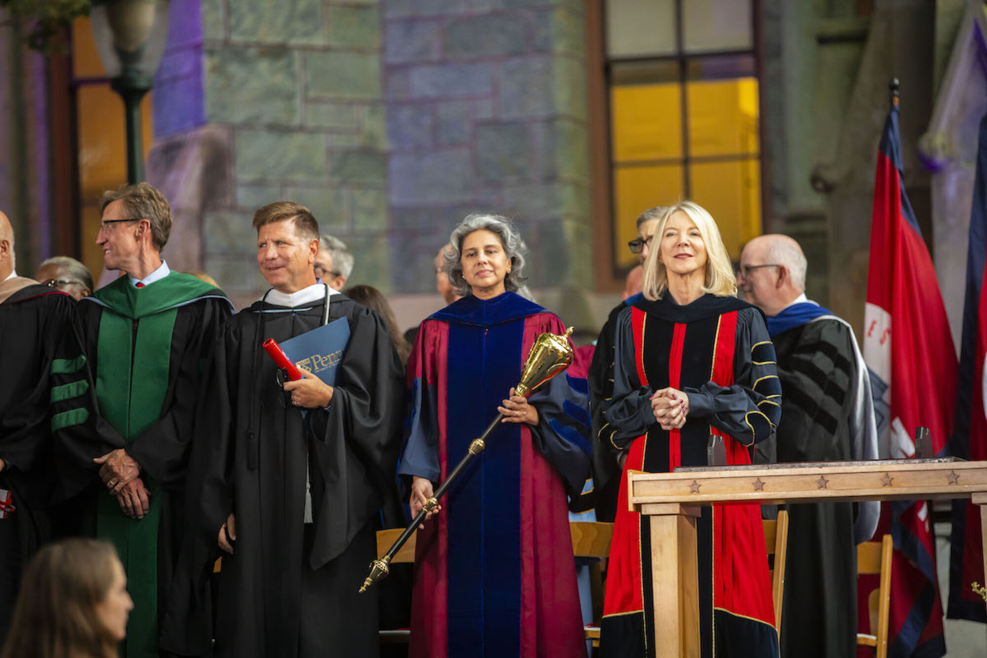 Several people in academic regalia onstage in front of College Hall, including Amy Gutmann at left and Medha Narvekar to her right, holding a mace.