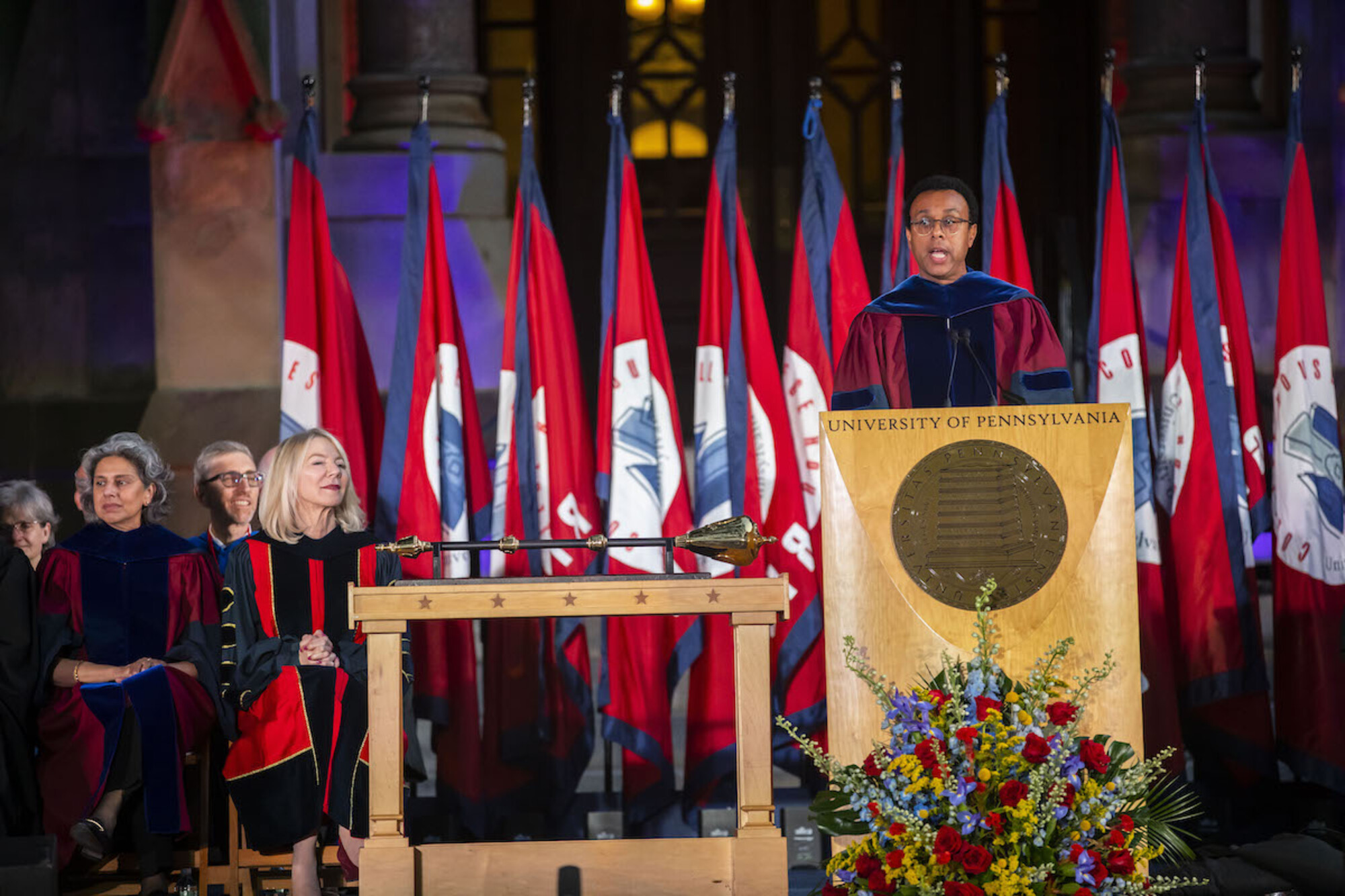 Penn Provost Wendell Pritchett speaks at the podium during convocation with Amy Gutmann and others seated to his right