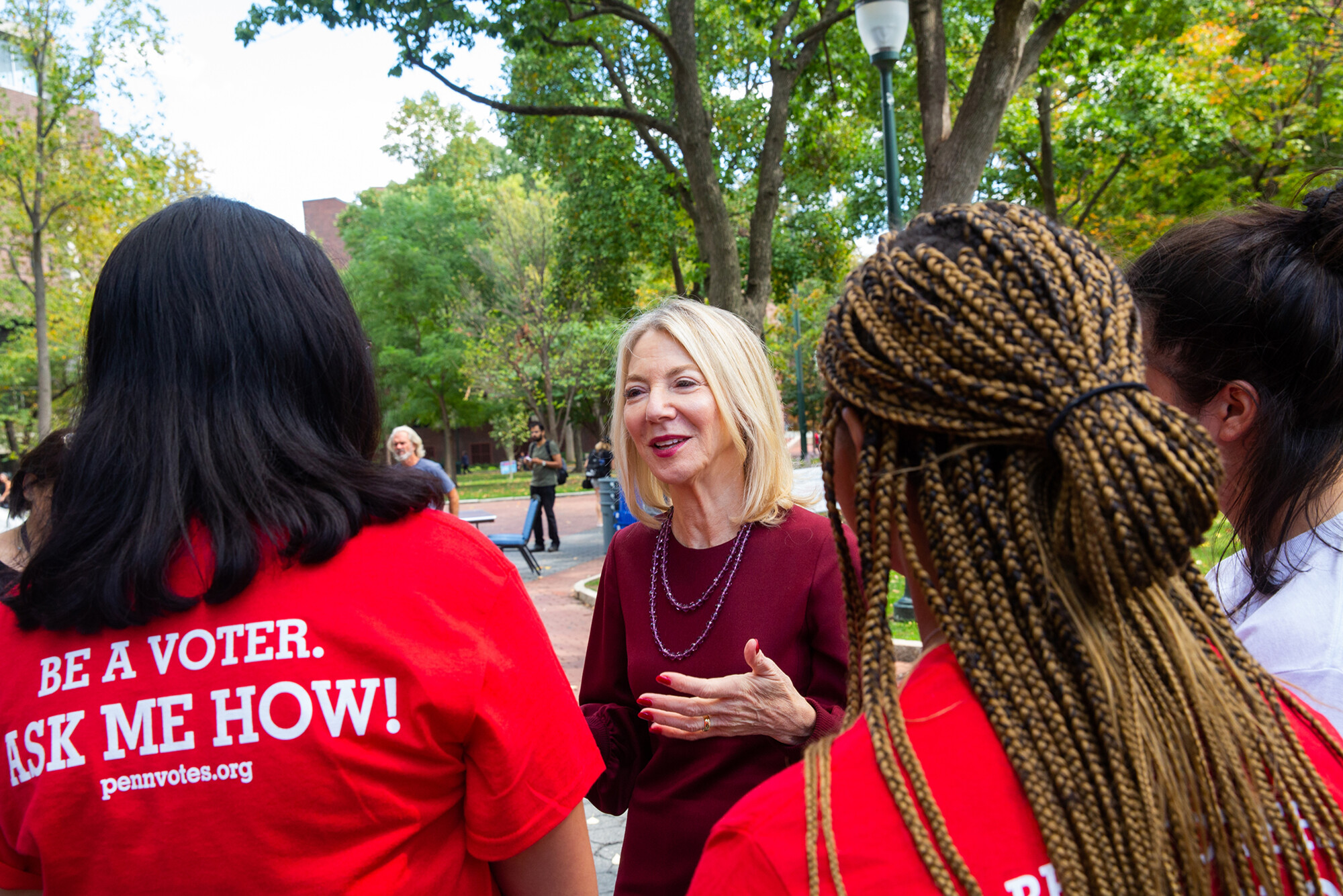 Amy Gutmann talks with two members of Penn Leads the Vote on College Green.