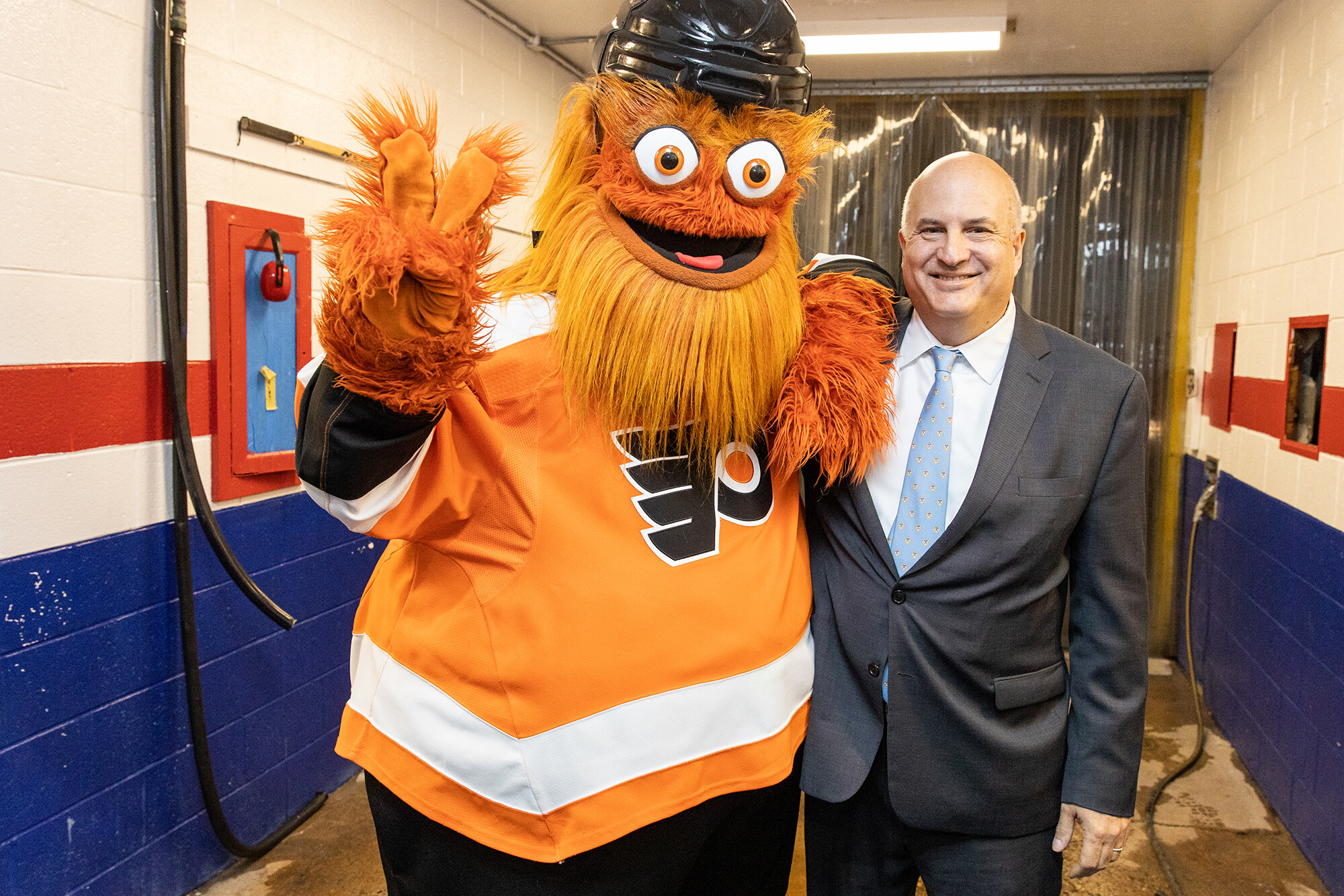 Gritty flashes the peace sign alongside Craig Carnaroli at the Penn Skating Rink