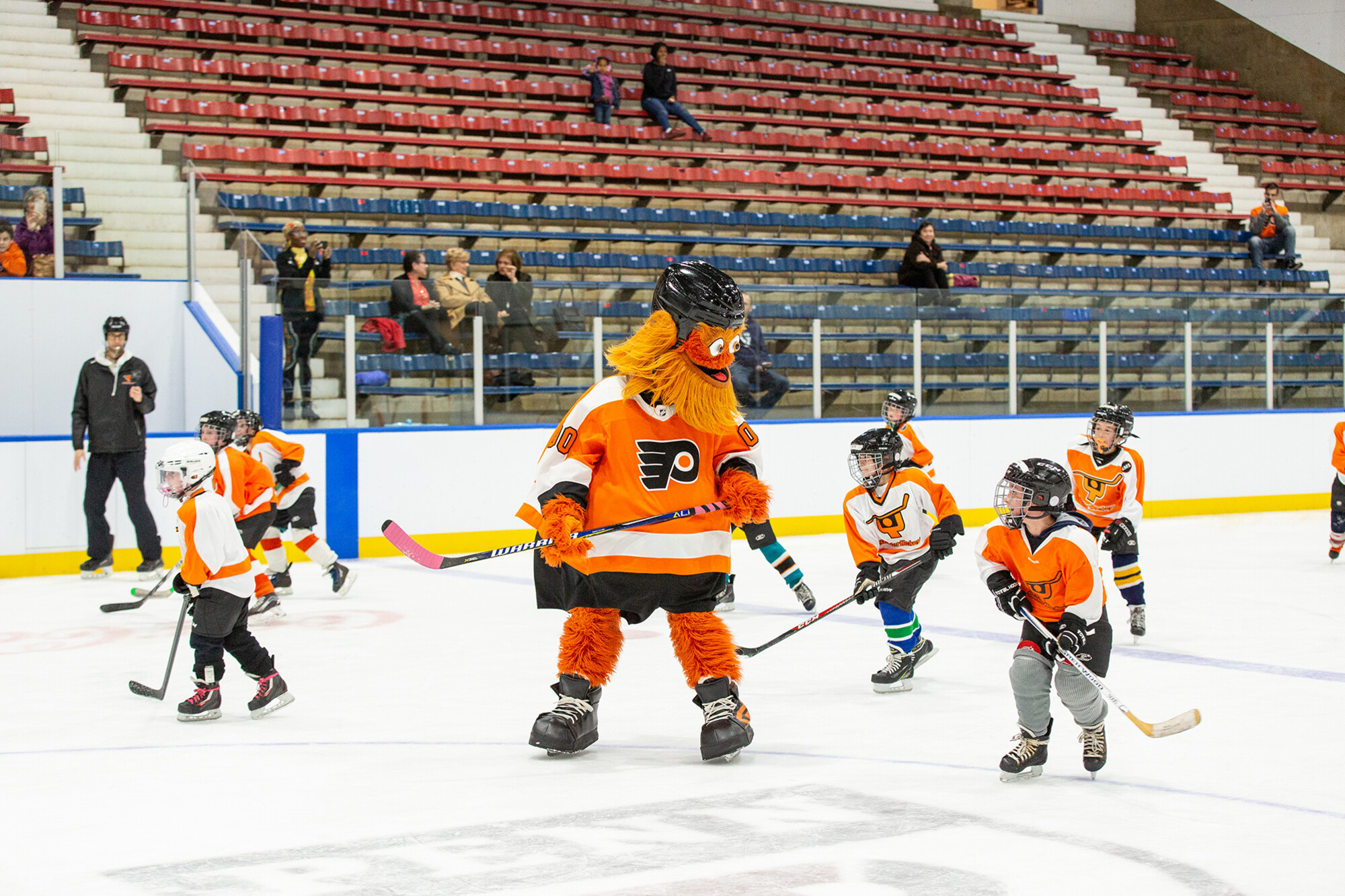 Gritty skating on the ice with members of a youth hockey league