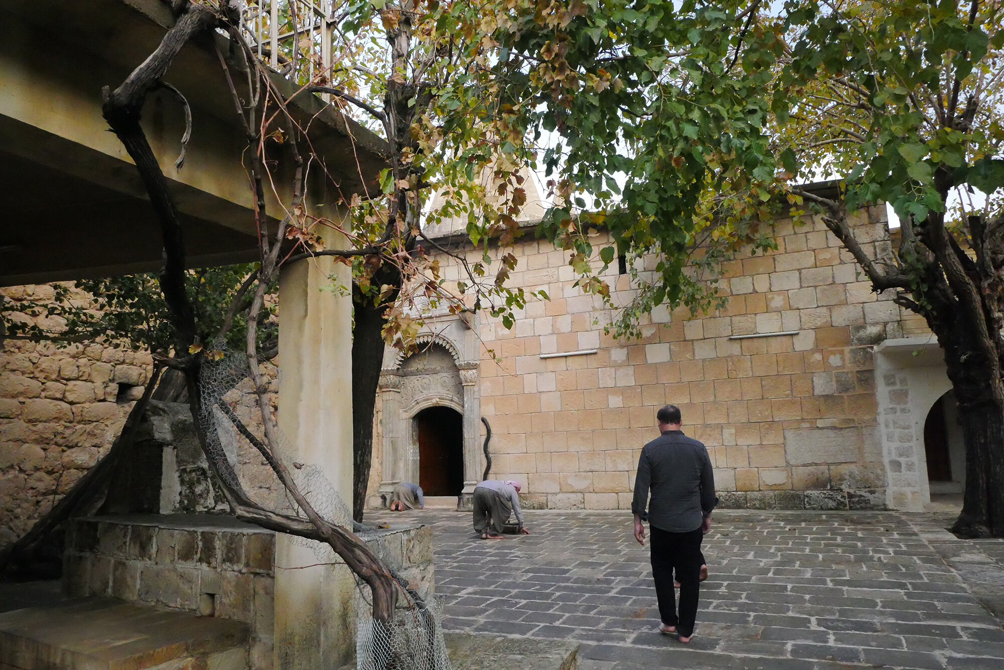 Two people in an outside courtyard at the Lalish Temple in daylight under a tree