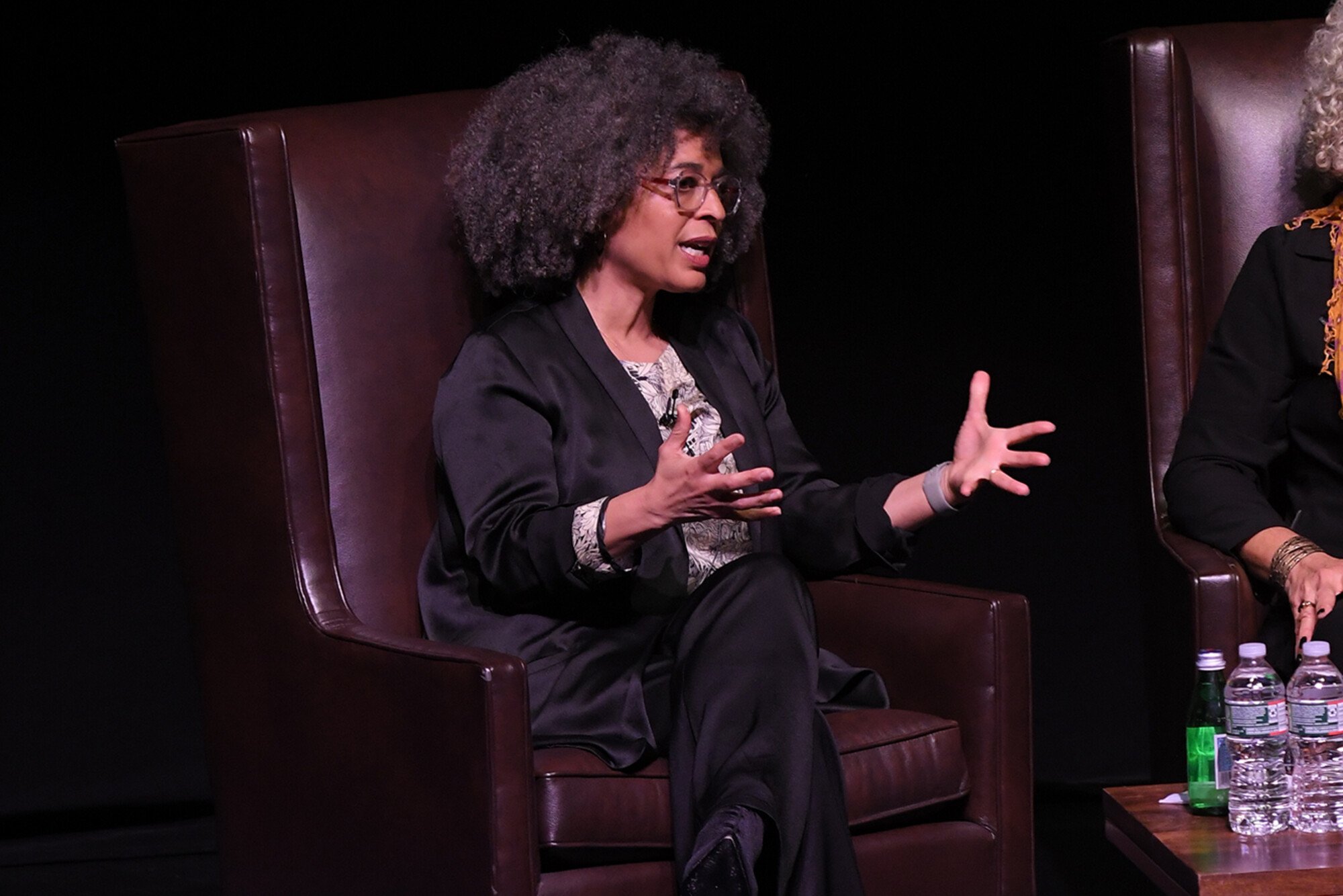 Gina Dent sits in a chair on stage with hands out in mid-sentence