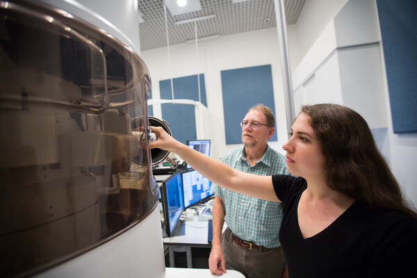 two researchers in front of large microscope in research lab