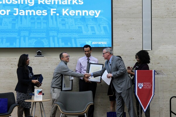 Mayor Kenney shakes hands with Daniel Hopkins on stage at Perry World House