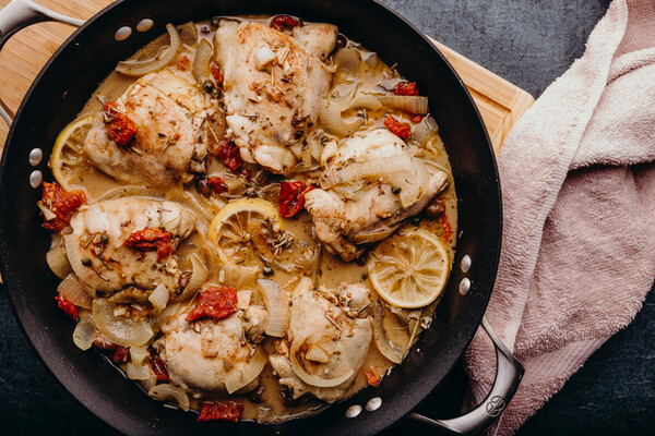 Chicken cacciatore in a large pot with a towel by its side