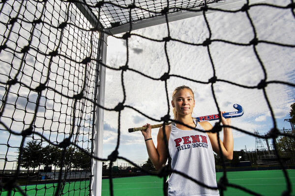 Schneck holding a field hockey stick posing on the field hockey field